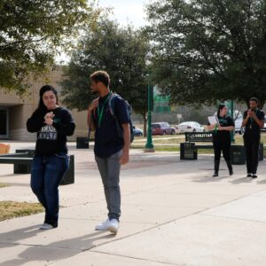 Students signing while walking on campus