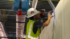 Man in safety vest drilling into wall