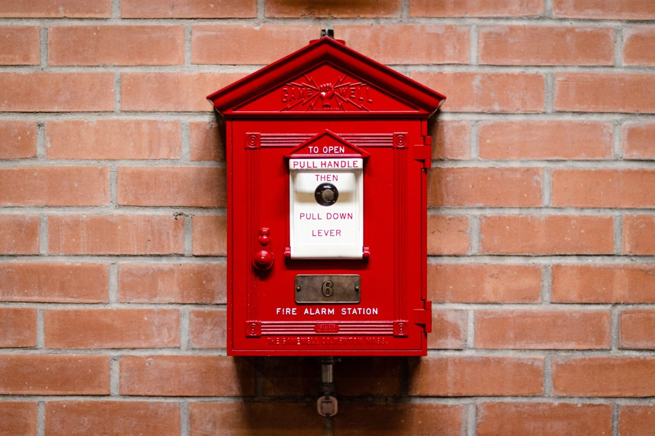 Old-fashioned fire alarm attached to brick wall
