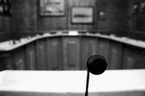 Greyscale image of microphone in foreground and meeting chambers in background