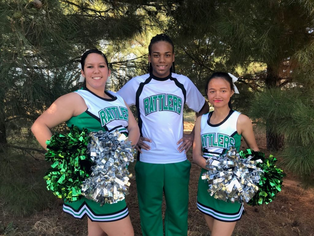 Three students in cheerleading uniforms