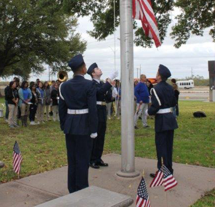 Three young men in military uniforms raise American flag